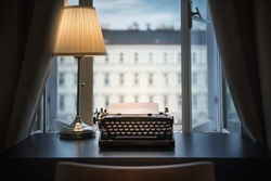 Workplace of a writer, journalist, creator. An old typewriter and a lamp on the table. Retro style. The concept on scientific, historical, literature, education and philosophical topics.