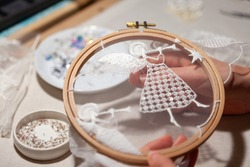 Workplace of an embroiderer with embroidery frames, angel embroidery, beads. The embroiderer's hands hold the embroidery hoop
