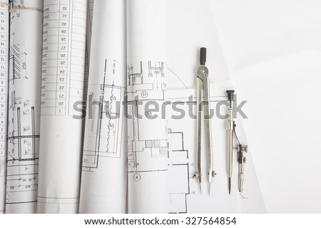 Workplace of architect - Architectural project, blueprints, blueprint rolls and divider compass on plans. Engineering tools view from the top. Construction background.