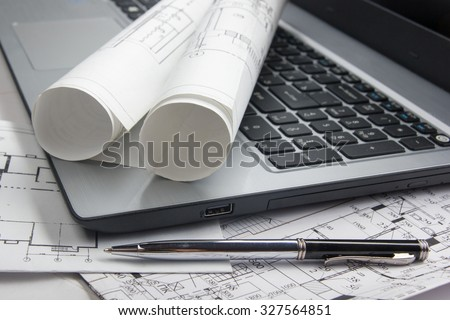Workplace of architect - Architectural project, blueprints, blueprint rolls and laptop ,pen on plans. Engineering tools and gadgets view from the top. Construction background.