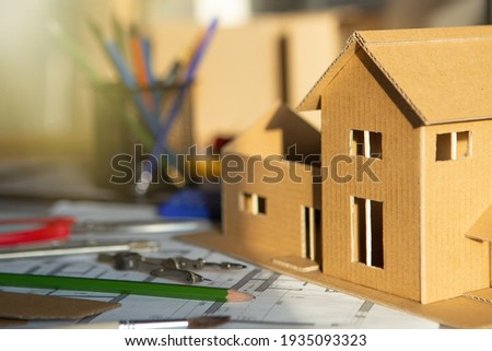 Workplace of architect - construction drawings, scale model and tools. Modern house design. Real estate concept.