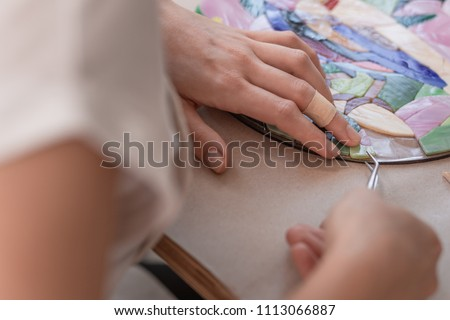 Workplace of the mosaic master: women's hands holding tool for mosaic details in the process of making a mosaic #1113066887