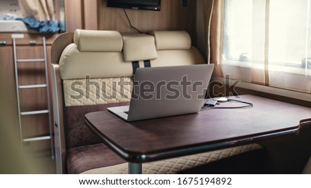 Workplace office campervan for freelancers nomad tele working inside camper van caravan online location independent lifestyle telework travel away from home. camper van, van life workspace quarantine