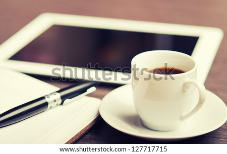 workplace, office desk: cap of coffee and tablet pc and notebook with pen