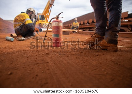 Workplace safety precaution stand by fire wash foots standing 1.5 m social distancing avoiding Coronavirus -19 with fire extinguisher in reach while defocused co worker conducting welding background