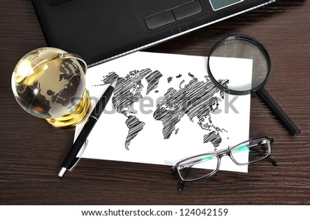 workplace with drawing world map on paper