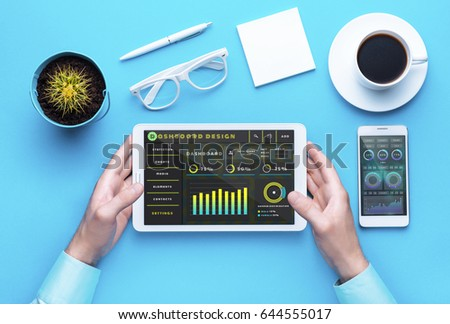 Workplace with office tools and gadgets. Cup of coffee on a table. Tablet, laptop, phone and camera to develop applications or other projects. White, black and yellow background. Flat layer photo. #644555017