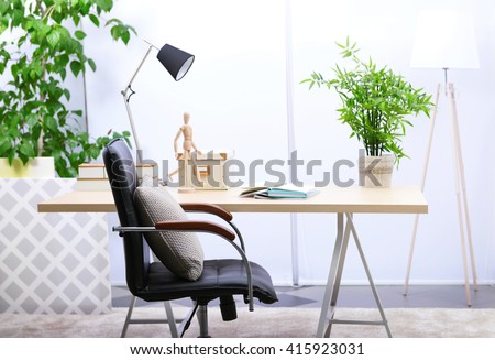 Workplace with table, office chair and lamp in living room