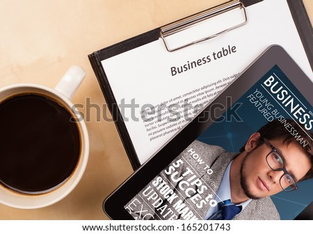 Workplace with tablet pc showing magazine cover and a cup of coffee on a wooden work table close-up