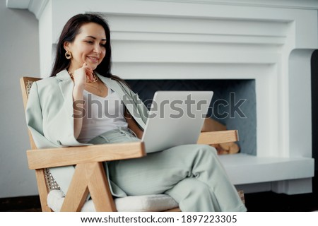 works online on a laptop computer, prints text to a project partner. The student manager is sitting on a chair of a young woman of Caucasian appearance. a favorite work, a comfortable business suit