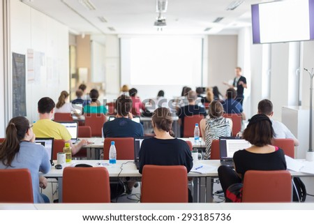 Workshop at university. Rear view of students sitting and listening in lecture hall doing practical tasks on their laptops. Stock photo ©
