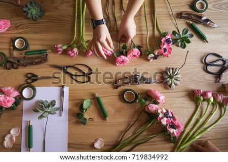 workshop florist. The hand of the girl on the background of the table with flowers. Create floral arrangements.