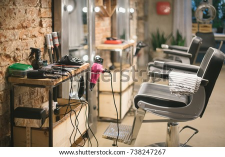 Workshop of hairdressers. Beauty salon with chairs, hair dryers, combs and mirrors