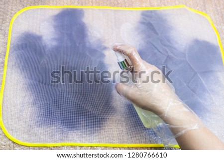 workshop of hand making a fleece gloves from blue Merino sheep wool using wet felting process - craftsman wetting first layer of fibers on cutting pattern through plastic mesh by spray