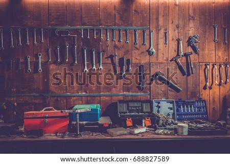 Workshop scene. Old tools hanging on wall in workshop, Tool shelf against a table and wall, vintage garage style