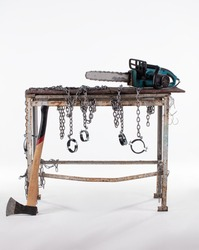 Workshop table with ax and chainsaw isolated on white background. The workbench table is decorated with iron chains.