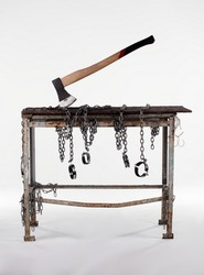 Workshop table with ax isolated on white background. The workbench table is decorated with iron chains.