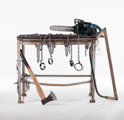 Workshop table with ax, jigsaw and chainsaw isolated on white background. The workbench table is decorated with iron chains.