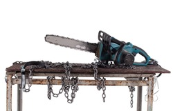 Workshop table with chainsaw isolated on white background. The workbench table is decorated with iron chains