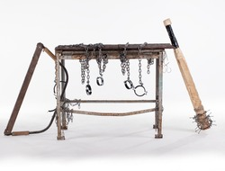 Workshop table with jigsaw and chainsaw isolated on white background. The workbench table is decorated with iron chains.