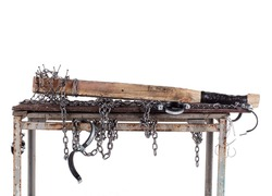 Workshop table with wooden bat with nails isolated on white background. The workbench table is decorated with iron chains.
