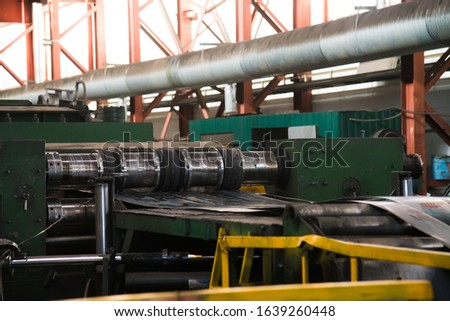 Workshop with machinery tools and equipment, rolls of steel for production metal pipes. Plant for the production of metal pipes. Stack of steel pipes.