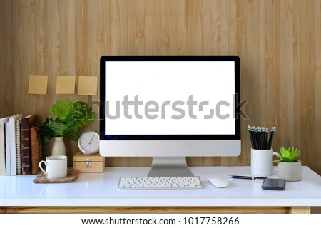 Workspace and blank screen desktop computer.Mockup desktop computer, coffee mug, plant and home office accessories on white desk.