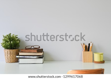 Workspace office table with books, glasses coffee and office supplies on white desk and wood chair.
