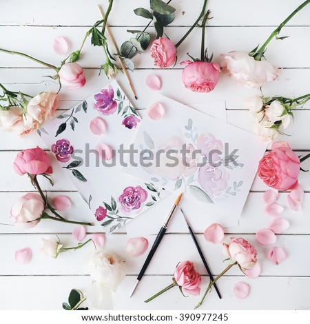 Workspace. Pink and red roses painted with watercolor, paintbrush and roses on white wooden background. Overhead view. Flat lay