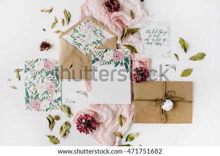 Workspace. Wedding invitation cards, craft envelopes, pink and red roses and green leaves on white background. Overhead view. Flat lay, top view #471751682