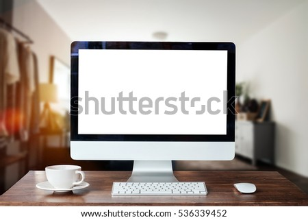 Workspace with blank screen coffee cup on a table in bright office room interior. #536339452