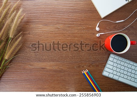 workspace with coffee, pencils, notebook, and grass on wooden table