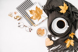 Workspace with golden maple leaves, notebook, coffee cup wrapped in scarf,  glasses. Stylish office desk. Autumn or Winter concept.  Flat lay, top view