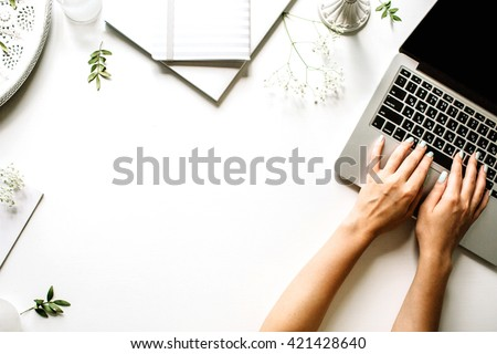 Workspace with laptop, girl\'s hands, notebook, sketchbook, white vintage tray, candlesticks on white background. Flat lay, top view. Freelancer working place