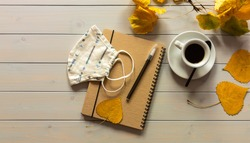 Workspace with notebook, mask, pen, autumn leaves, and coffee cup. Flat lay, top view wooden table desk.