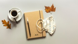 Workspace with notebook, pen, autumn leaves, and coffee cup. Flat lay, top view wooden table desk.