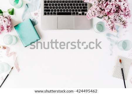 Workspace with paintbrush, laptop, lilac flowers bouquet, spool with beige and blue ribbon, mint diary on white background. Flat lay, top view
