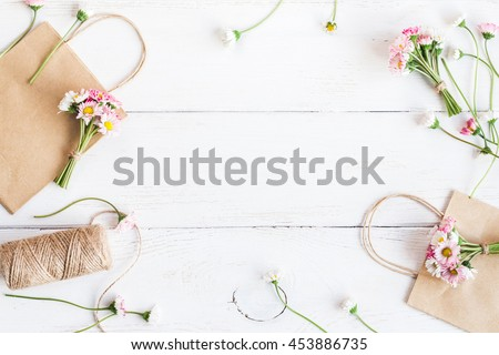 Workspace with small bouquets of daisy flowers, paper packages. Creative flowers. Top view, flat lay