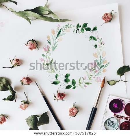 Workspace. Wreath frame with flowers and leaves painted with watercolor, paintbrush and pink roses isolated on white background. Overhead view. Flat lay, top view