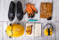 Workwear for a production worker on a white table. Personal protection accessories and electric tools used at work. Light background.