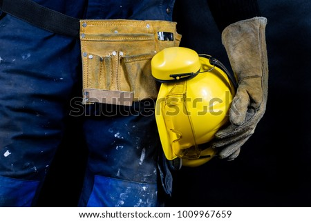 Workwear for production workers. A construction worker holding protective accessories. Black background.