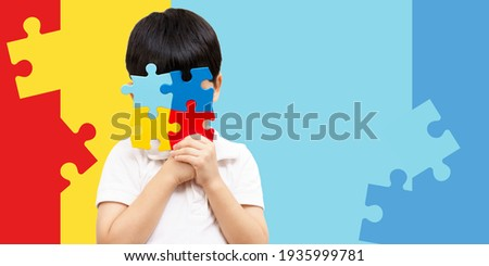 World autism awareness day April 2 - Studio Portrait of a cute asian boy cover his face with the colorful puzzles pieces. Autism Spectrum Disorder concept, ASD, Syndrome, Light it up blue, Backdrop.