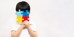 World autism awareness day April 2 - Studio Portrait of a little cute asian child cover his face with the colorful puzzles pieces. Autism Spectrum Disorder concept, ASD, Syndrome, Symptoms, Copy space