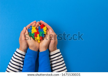 World autism awareness day concept. Adult and child hands holding puzzle heart on light blue background