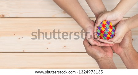 World Autism Awareness day, mental health care concept with puzzle or jigsaw pattern on heart with autistic child's hands supported by nursing family caregiver parent