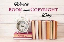 World book and copyright day, april 23. Poster with vintage alarm clock and pile of books on wooden table.
