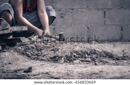 World Day Against Child Labour concept: Poor little boy working at construction site