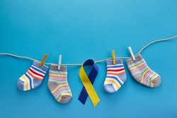 World Down syndrome day background. Down syndrome awareness concept. Socks and ribbon on blue background