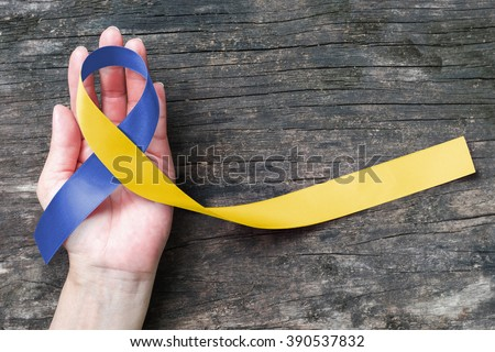 World down syndrome day with blue yellow awareness ribbon bow color on helping hand for raising support on patient with down syndrome illness disability and Thoracic Outlet Syndrome - (TOS) #390537832