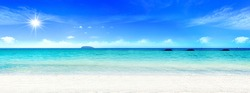 World Environment Day concept: Beautiful beach with white sand, turquoise ocean water and blue sky with clouds in sunny day